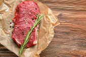 Fresh raw meat with spice on parchment paper poster