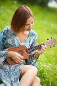 Young Woman In Bohemian Dress Play On Ukulele poster