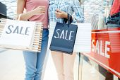 Young friendly women in casualwear holding shopping-bags after black friday sale poster