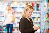 stock photo of grocery-shopping  - Young woman smiling while shopping in the supermarket with people in the background - JPG