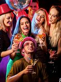 Dance party with group people dancing. Women and men have fun in night club. Happy girl on foregroun poster