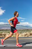 Triathlon runner triathlete man running in tri suit at ironman competition race on road. Sport athle poster