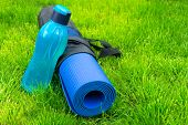 A Bottle Or Water On A Yoga Mat On Fresh Green Grass. The Concept Of Training And Recreation. Sports poster