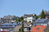 Several Roofs Of Houses With Solar Panels Under The Blue Sky. Solar Panels On Roofs With Tiles poster