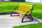 Bench With Iron Black Legs And A Brown Colored Wooden Seat On A Stone Sidewalk In The Background Beh poster
