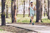 Handsome Man In Sportswear Running Along Walkway In Sunny Park poster