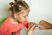 Cute Little Girl Looking At Trimming Her Fingernails By Manicure Scissors poster