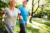 Mature Couple Jogging And Running Outdoors In City poster