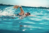 Professional Triathlete Swimming In Rivers Open Water. Man Wearing Swim Equipment Practicing Triathl poster