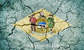 State Of Delaware Flag, State Located In The Mid-atlantic Region Of The United States, On Dry Earth  poster