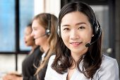 Smiling Beautiful Asian Woman Telemarketing Customer Service Agent Working In Call Center With Her M poster