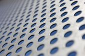 Bright brushed and drilled a hole metal texture over a blue background (selective focus, photographed with shallow DOF)