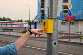 The Hand Of A Girl With A Clock Presses The Button Of The Pedestrian Crossing. A Hand Sign Indicates poster