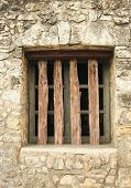 stock photo of scrappy  - An old window with wood bars cased into stone - JPG