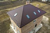 Aerial Top View Of Building Steep Brown Shingle Roof, Brick Chimneys And Small Attic Windows On Hous poster
