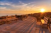 Weathered lumber path leading to calm sea during beautiful sunset in countryside in Cabopino, Artola poster