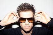 Trendy young man with spiky hair with his hands raised to a pair of sunglasses.