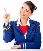 Beautiful air hostess pointing with her finger - isolated over a white background
