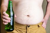 Thick Male Belly. A Man Holds A Bottle Of Beer In His Hand Against The Background Of His Thick Torso poster