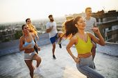 Group Of Happy Fit Young People Friends In Sportswear Doing Exercises . Sport Outdoors poster