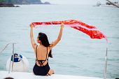 Back View Of Young Brunette Woman Swinging Bright Red Pareo Sitting On Yacht In Calm Sea poster
