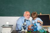 Child Pupil And Old Teacher Using Microscope. Back To School And Home Schooling. Old Teacher Near Ch poster