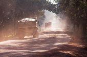 foto of tatas  - Heavy trucks on red dusty road India Karnataka - JPG
