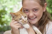 foto of fondling  - a young girl holding her cat in the garden - JPG