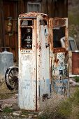 stock photo of bowser  - Very old rusty derelict petrol pump with analog dials - JPG