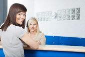 Portrait of smiling young woman with receptionist in dentist's office