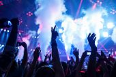 Picture of rock concert, music festival, New Year eve celebration, party in nightclub, dance floor, disco club, many people standing with raised hands up and clapping, happiness and night life concept