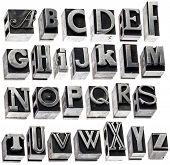 English alphabet - a collage of 26 isolated letters in grunge letterpress metal type block, a variety of fonts