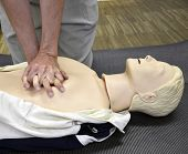image of cpr  - A man practicing CPR techniques on dummy - JPG