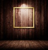 grunge wooden interior with a spotted golden picture frame.