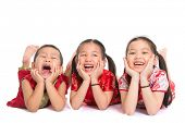 Group of happy young Asian children in traditional Cheongsam dress lying on floor with head on hands