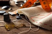 stock photo of sewing  - Sewing accessories on old wooden table background - JPG