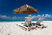stock photo of beachfront  - Sun umbrella with chair longues on tropical beach - JPG