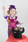 Little girl in costume magician waves her wand over the cylinder with kittens