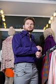 A man with beard in a blue shirt and gray trousers, trying on clothes in a clothing store