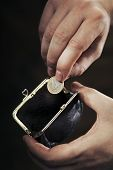 Man taking the last Euro coin from his small change purse. Very short depth-of-field.
