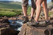 Couples feet standing at edge of river wearing hiking gear