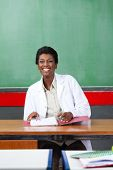 Happy young African American teacher looking away while sitting with binder at desk in classroom