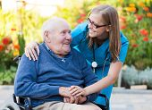 stock photo of grandfather  - Kind doctor taking care of an old man in wheelchair - JPG
