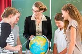 Students or pupils having group work while geography lesson and the teacher test or educate them in