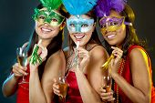 stock photo of african mask  - beautiful three women having fun during party on dark background - JPG