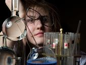pic of flask  - She sits behind a mountain disheveled test tubes and flasks - JPG