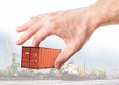 Bright Red Metal Freight Shipping Container In Man's Hand Above Port Background