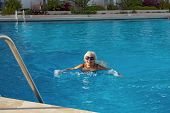 Aged Woman Is Swimming In Blue Water Of Resort  Pool.