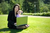 Young Lady With A Baby And A Notebook In A Park