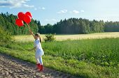 image of hazy  - Little girl with a bunch of red balloons walking on a country road in a green summer landscape with hazy vintage editing - JPG
